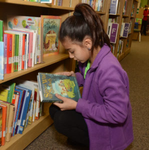 Student looking at book near a shelf.
