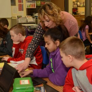 Teacher showing students how to use catalog on computer
