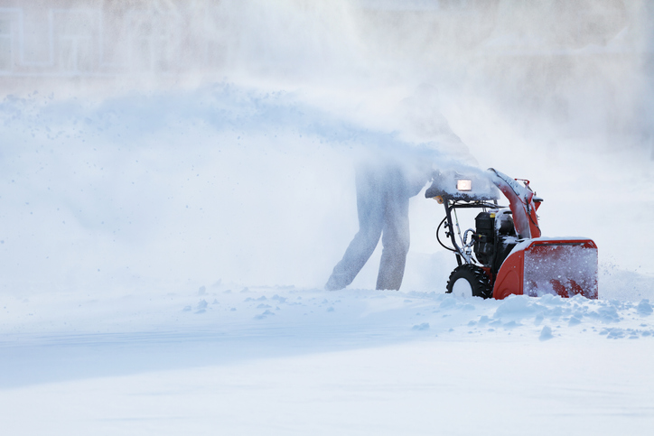Photo of a person clearing snow with a snow plow