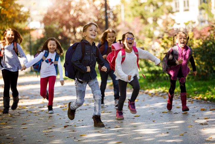 School kids running near a school